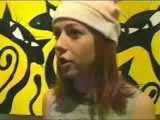 Portant un bonet faisant comme des oreilles devant une toile au fond jaune stylisant des chats noirs