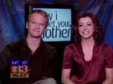 Alyson Hannigan à coté de Niel avec en fond de décor un grand écran affichant le titre de la série