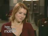 Alyson Hannigan souriante en pull grenat sur le plateau de How I met your mother